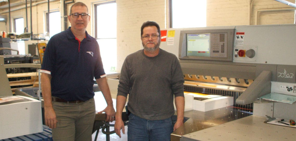 Production manager Tom Reginer (left) and operator Agustin Roque with the Polar X115 paper cutter.
