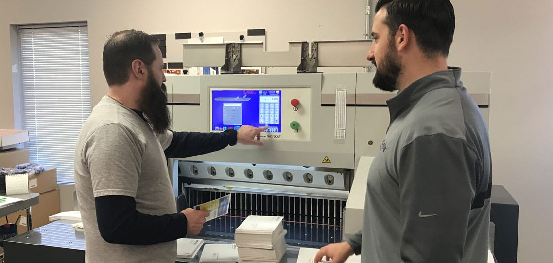 Bindery lead Mark Mullen and Jon Mullins with new PRISM paper cutter