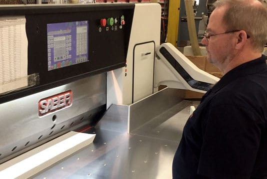 Joe Ward works on the new SABER paper cutter at The YGS Group in York, Pennsylvania.