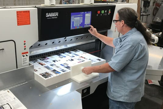 Kevin Chapman cuts work on the new 54-inch SABER X-15 paper cutter at MPress.