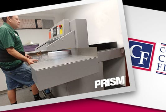 Print specialist working on the new PRISM paper cutter in the print shop