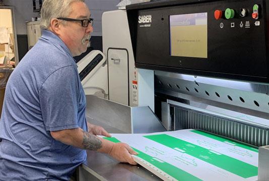 Worker operating a SABER paper cutting machine