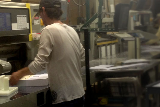 Two bindery veterans at work on PRISM paper cutters at Boelte-Hall.